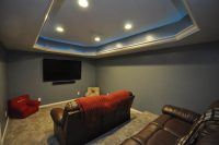 Basement theater room with seating platform and custom lighting