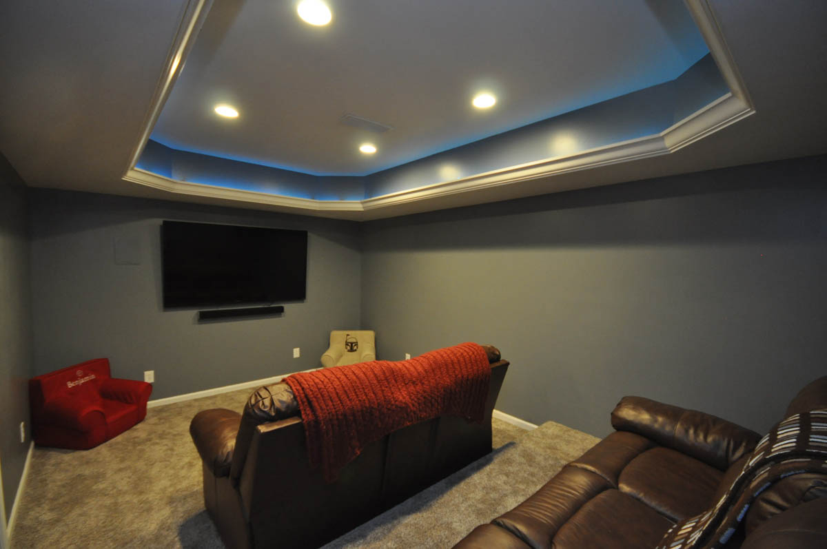 Basement theater room with seating platform and custom lighting