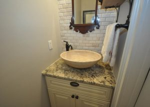 Powder room remodel with new flooring, vanity, granite top, stone vessel sink and backsplash