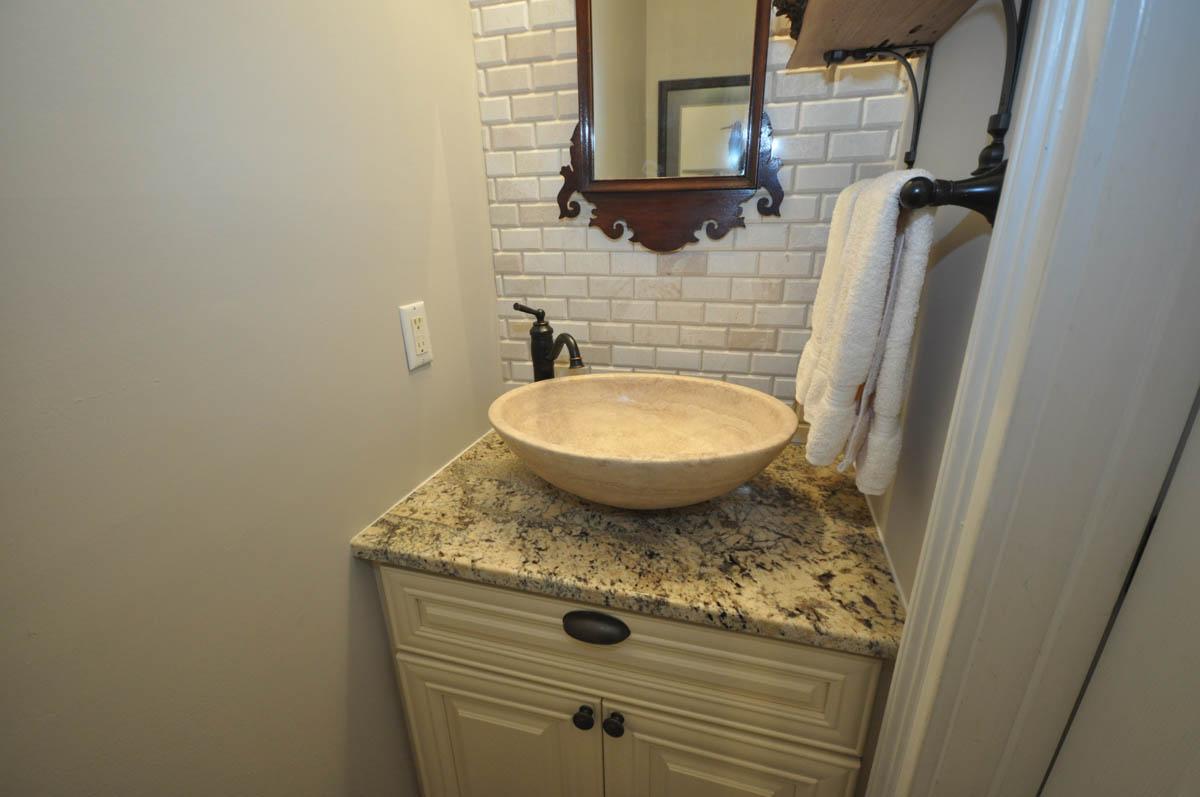 Powder room remodel with new flooring, vanity, granite top, stone vessel sink and backsplash